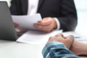Lender reviewing documents from man looking to receive a loan