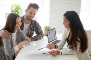 Couple in office discussing finances with female businesswoman