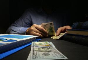 Loan shark counting money in dark room