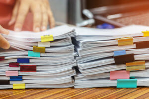 Business man hands reviewing stacks of paperwork on desk