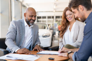 Happy couple and car salesman signing paperwork for a car