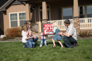 Family in front of new home with Sold Home for Sale sign