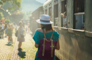 Woman with backpack getting off of a train while traveling