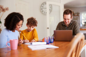 Family works on budget together at dining room table