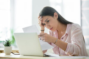 Woman looking at bills on laptop stressed out