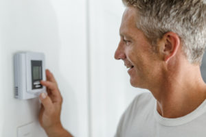 Man lowering his heating thermostat
