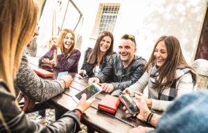 Millennial friend group having fun using their smart phones