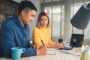 Young couple at desk working on taxes