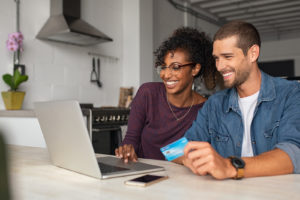 Smiling young couple using credit card on laptop in kitchen