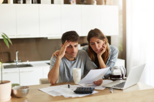 Unhappy Couple Managing Home Accounts In Kitchen