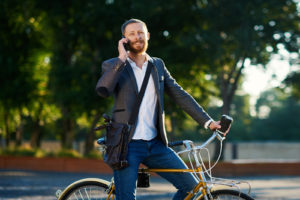 A young businessman biking and talking on the phone