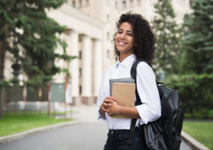 Happy student standing on campus holding her books