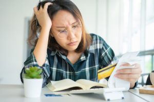 Woman stressed out looking at credit card bills